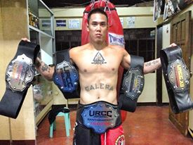 Galera holding URCC belts of teammates at Lakay and his own belt wrapped around his waist